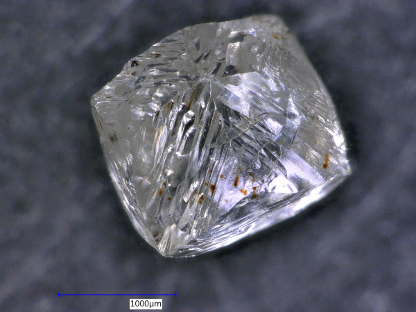 This octahedral diamond cyrstal looks like it has been faceted. These are all growth textures on the triangular crystal faces.