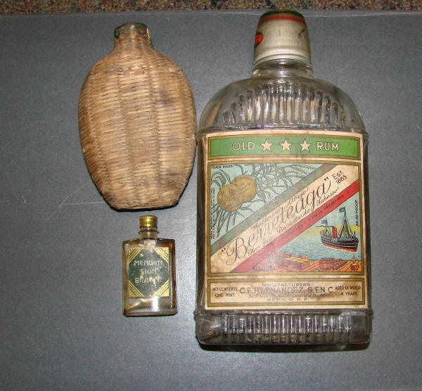 Empty bottles of rum. One bottle is covered with woven wicker.